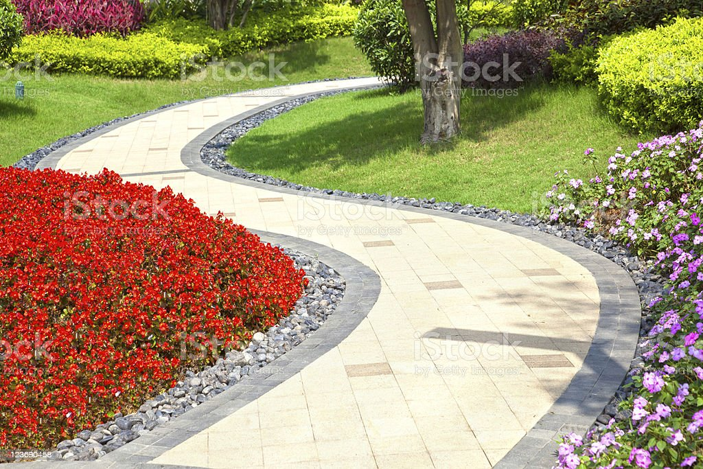 Bright summer garden planted alongside winding tile walkway stock photo