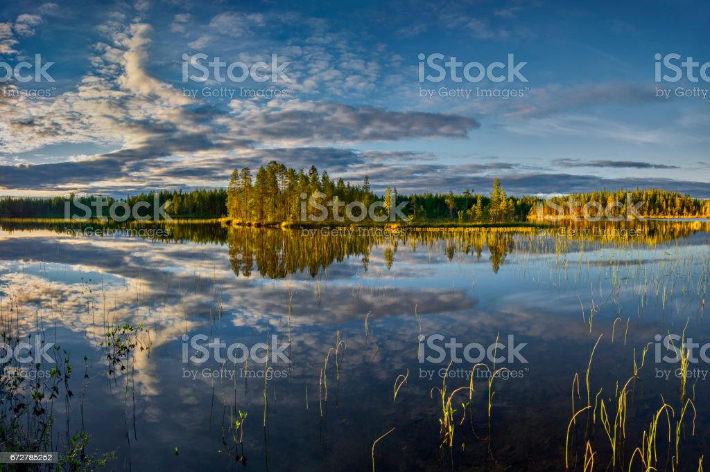 Bright summer sunset over the lake in the woods, Sweden around town Dorotea stock photo