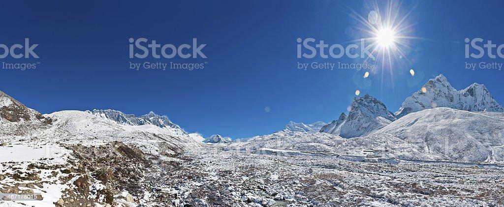 Bright sun flaring over white mountain peak wilderness panorama Himalayas royalty-free stock photo
