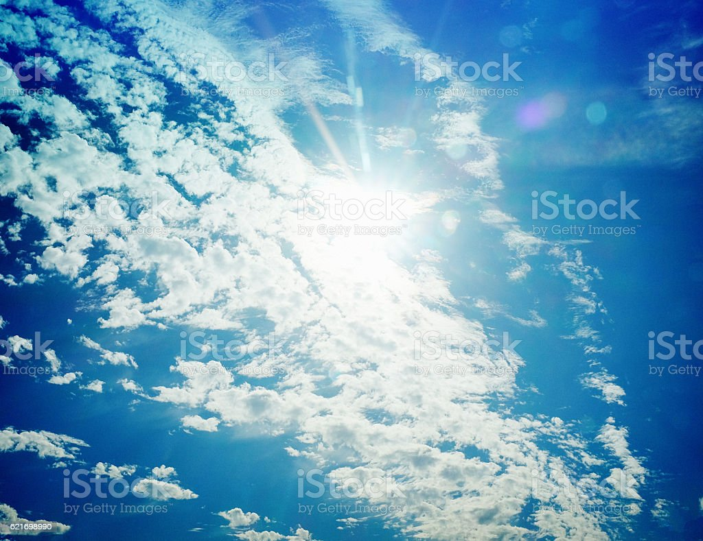 Bright sun masked by  floating cirro-cumulus clouds stock photo