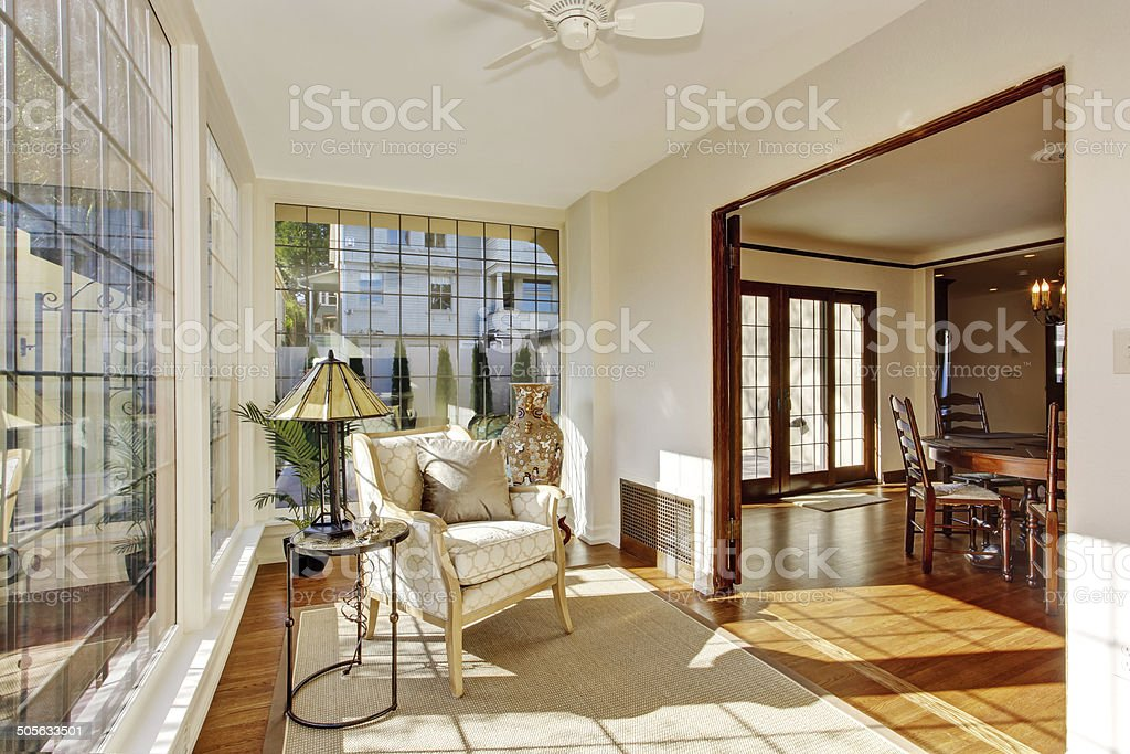 Bright sunroom with antique chair stock photo
