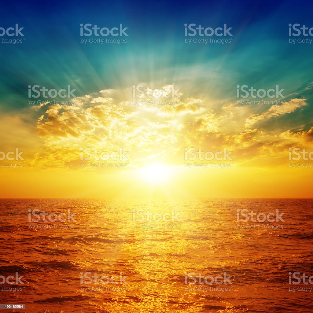 bright sunset in dramatic sky over sea stock photo