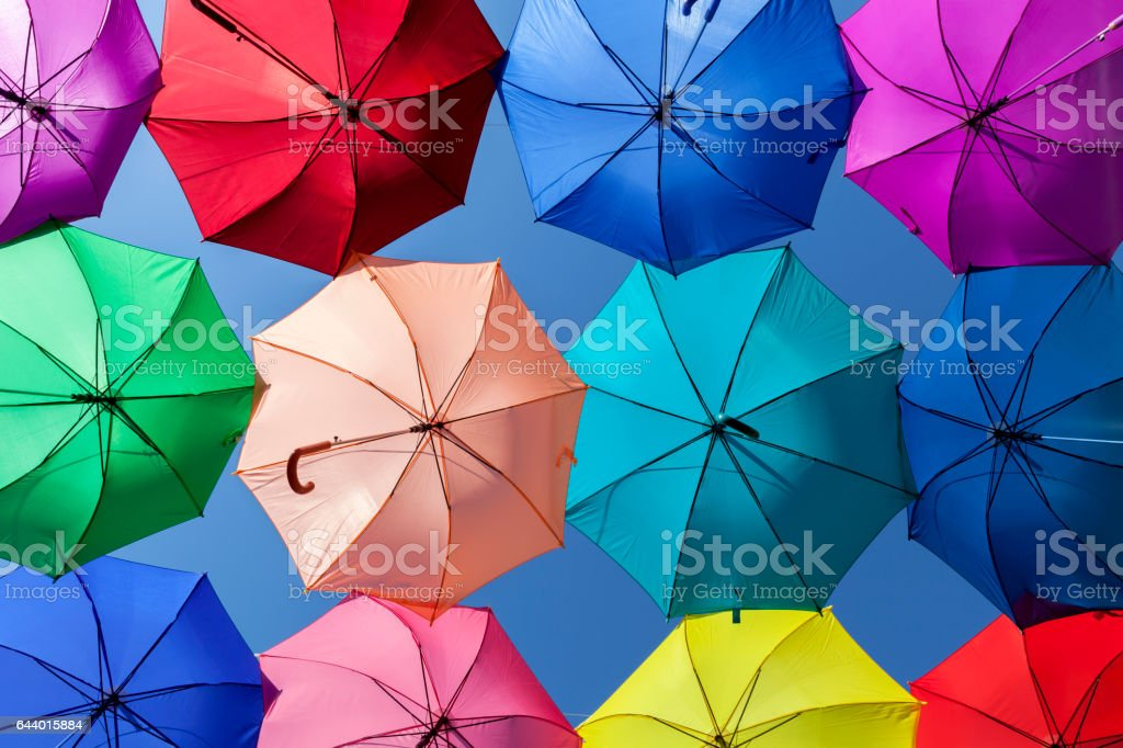 Bright vibrant colorful umbrellas parasols row pattern blue sky background stock photo