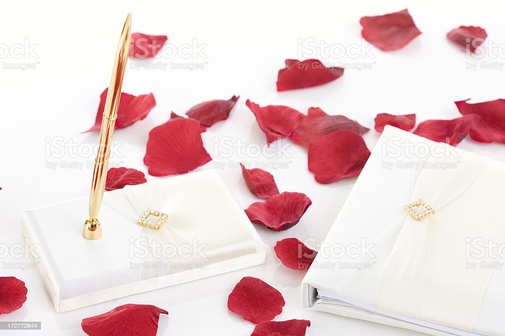 Bright White Wedding Pen and Guest Book with Rose Petals royalty-free stock photo