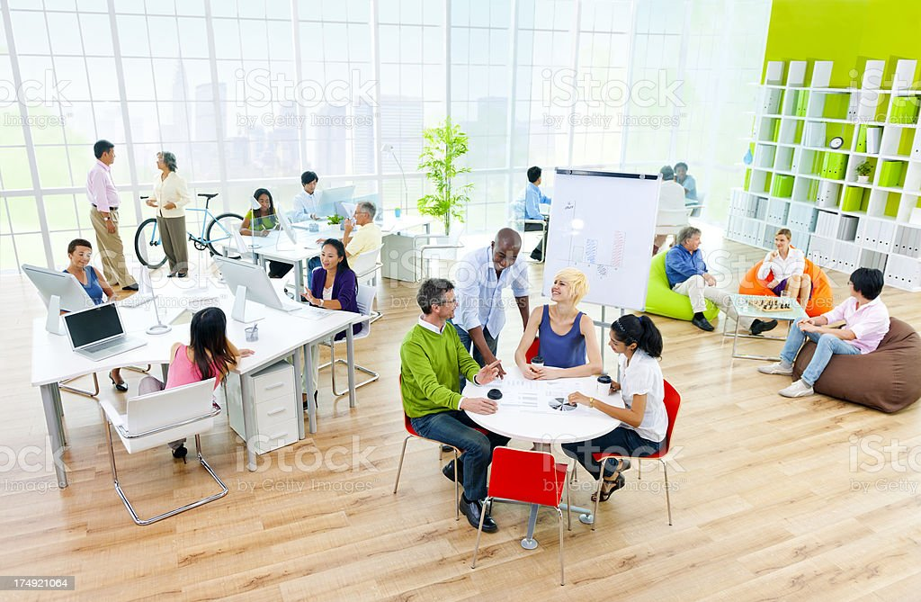 Bright workspace with meeting tables, people collaborating royalty-free stock photo