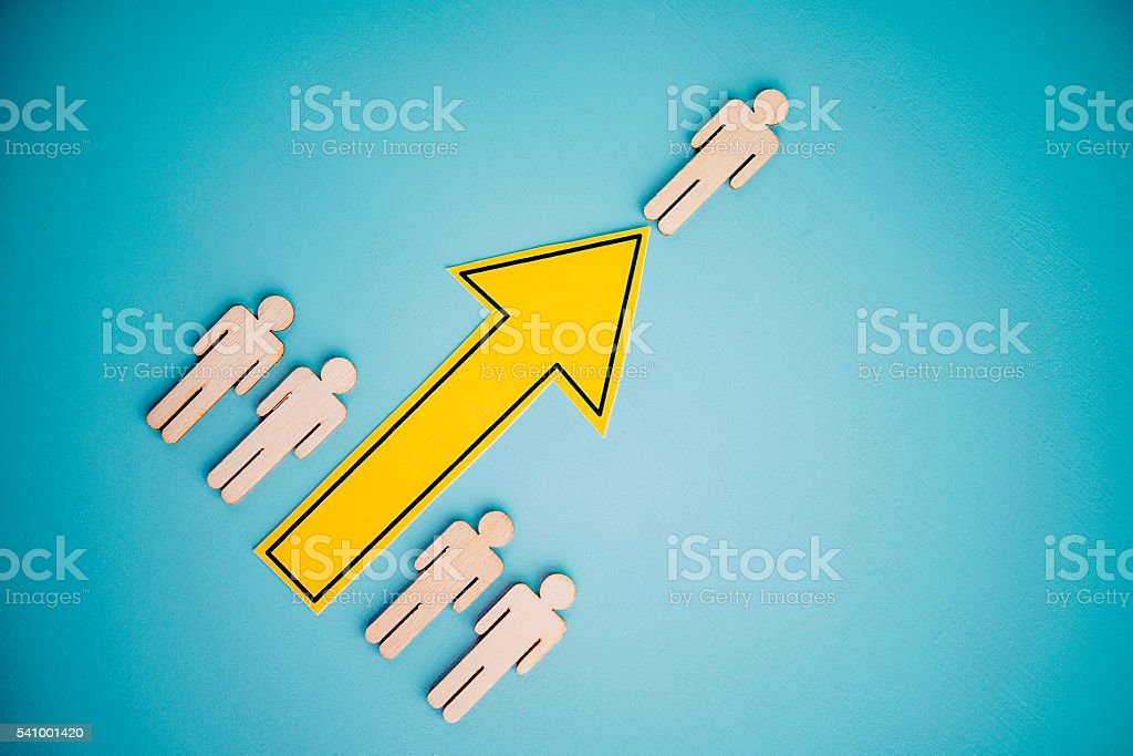Bright yellow arrow with male figure at top. Leadership concept stock photo
