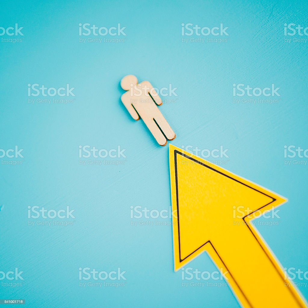 Bright yellow arrow with male figure moving upwards stock photo