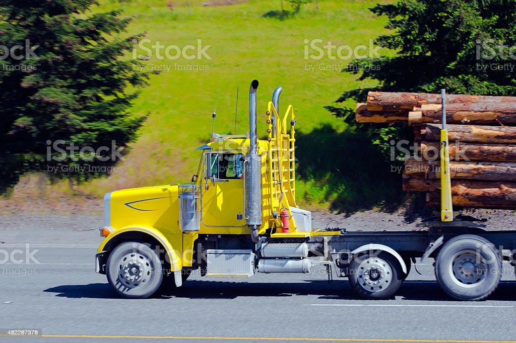Bright yellow big rig semi truck cargo logs stock photo