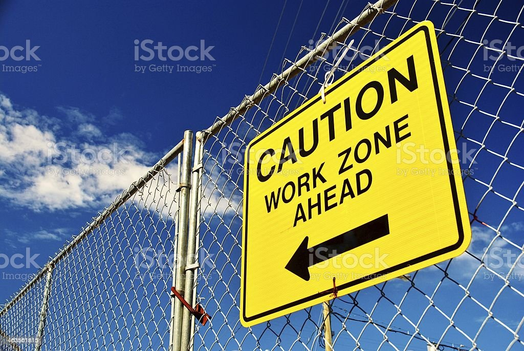 A bright yellow caution work ahead sign on a fence stock photo