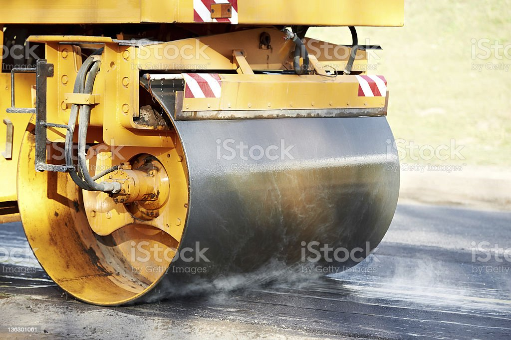 Bright yellow compactor roller at asphalting work stock photo