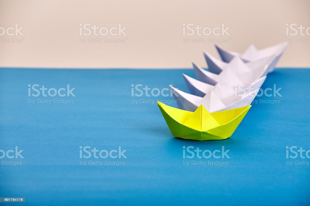 Bright yellow paper ship leading white ones based on blue against...