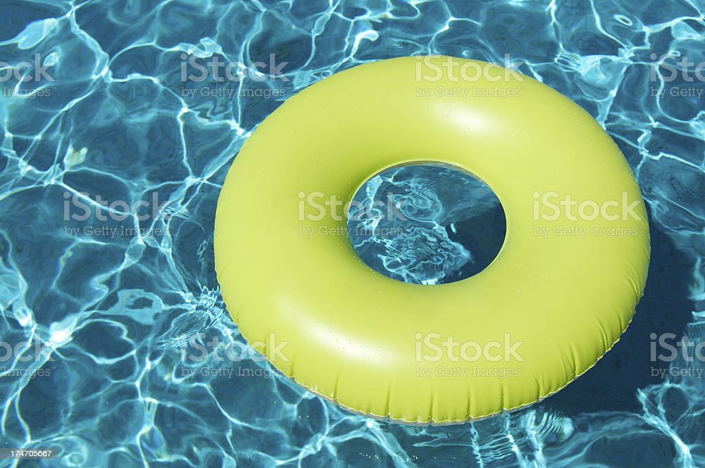 Bright Yellow Pool Ring Floating on Blue royalty-free stock photo