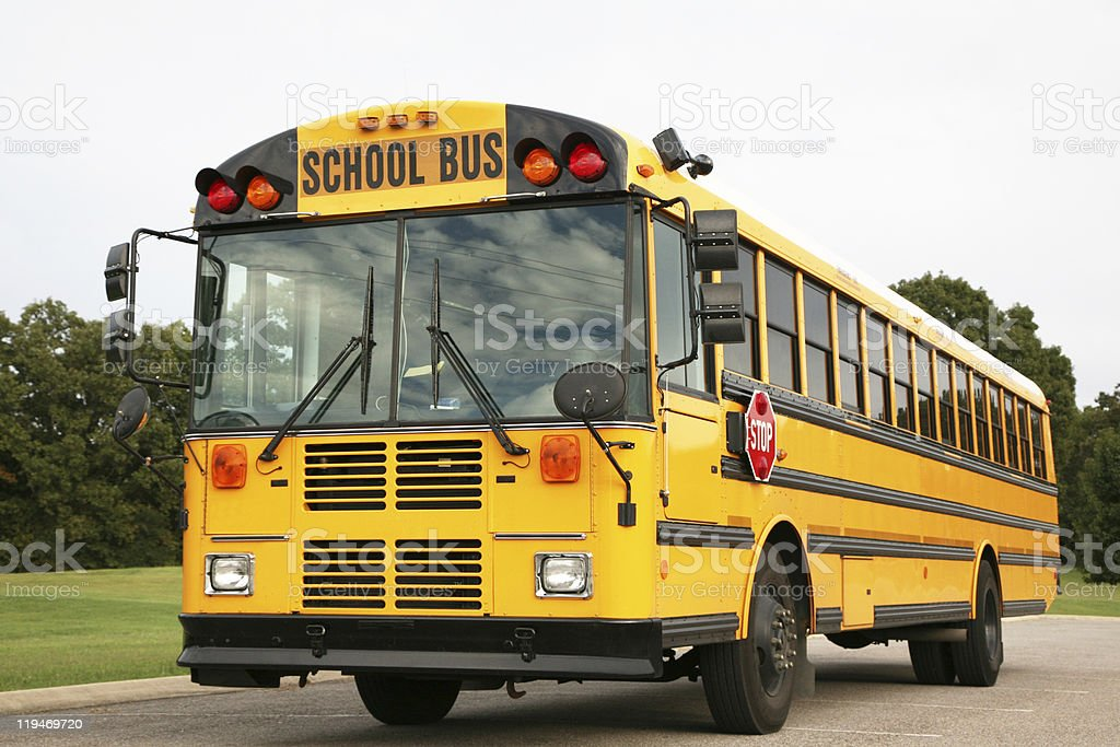A bright yellow school bus ready to pick up school children royalty-free stock photo