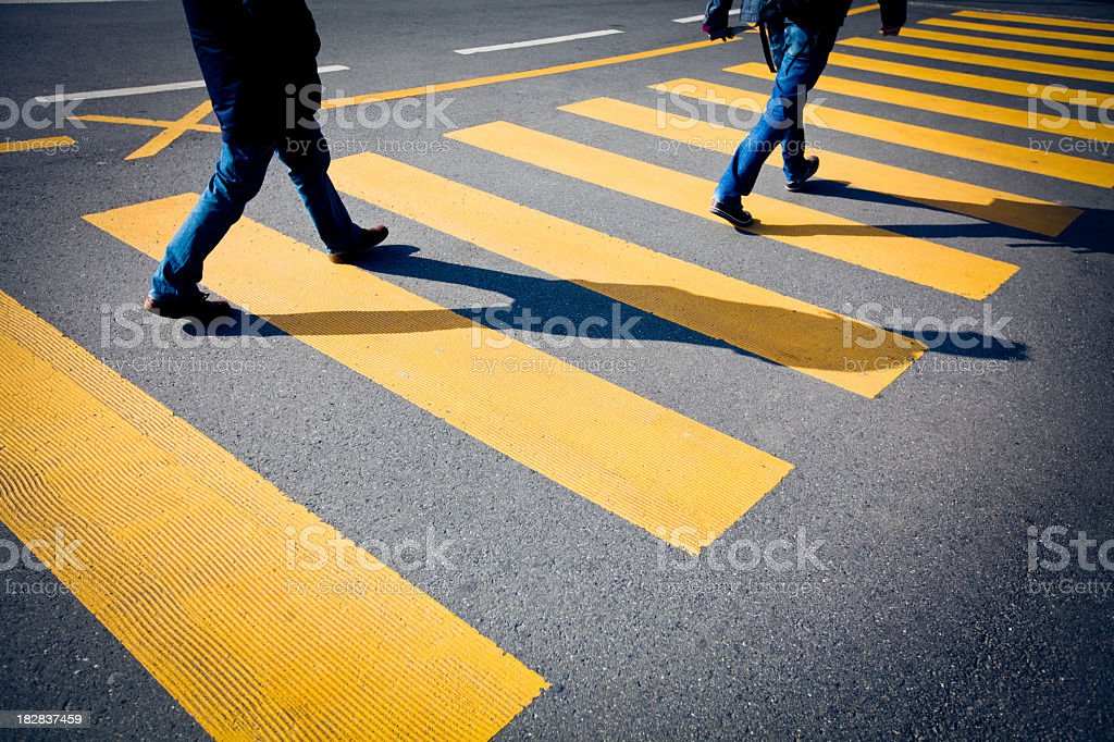 Bright yellow segmented crosswalk being used by pedestrians royalty-free stock photo