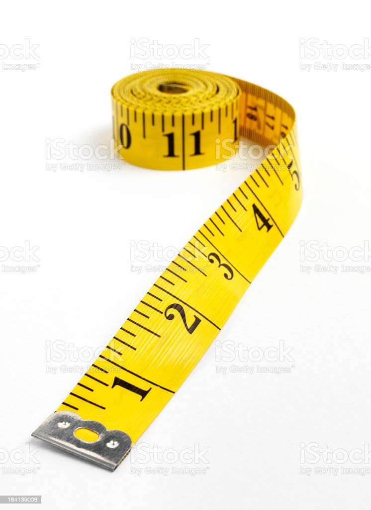 A bright yellow tape measure in inches royalty-free stock photo