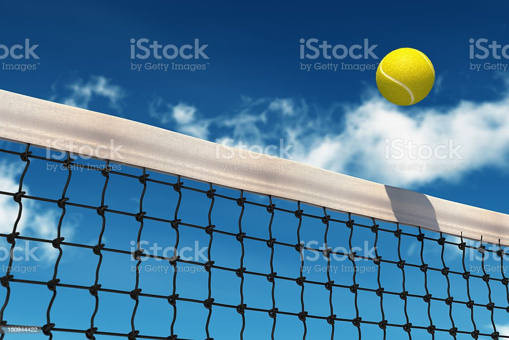 Bright yellow tennis ball going over net on a beautiful day royalty-free stock photo
