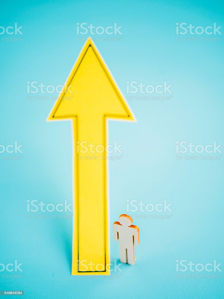 Bright yellow UP arrow against blue background with male figure stock photo