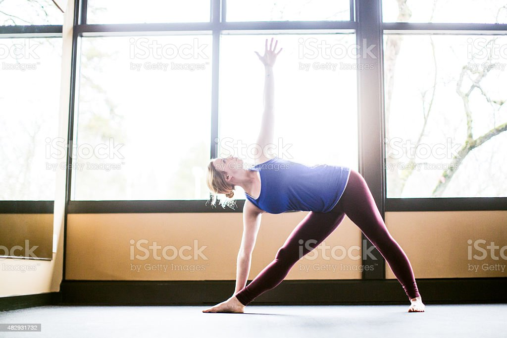 Bright Yoga Studio and Woman Practicing stock photo