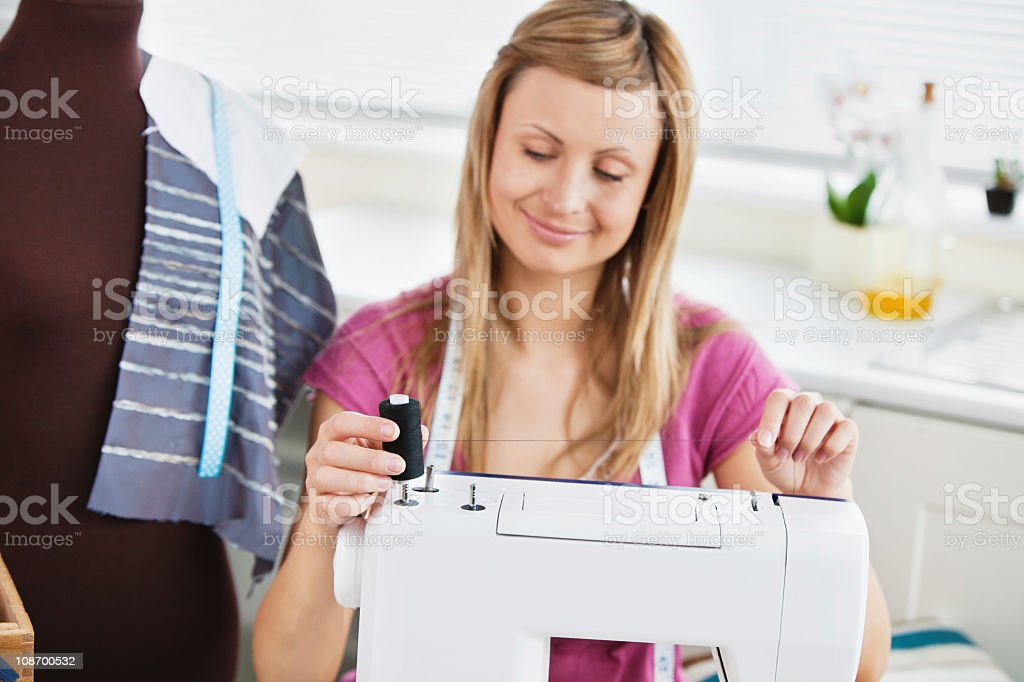 Bright young woman using her sewing machine in the kitchen royalty-free stock photo