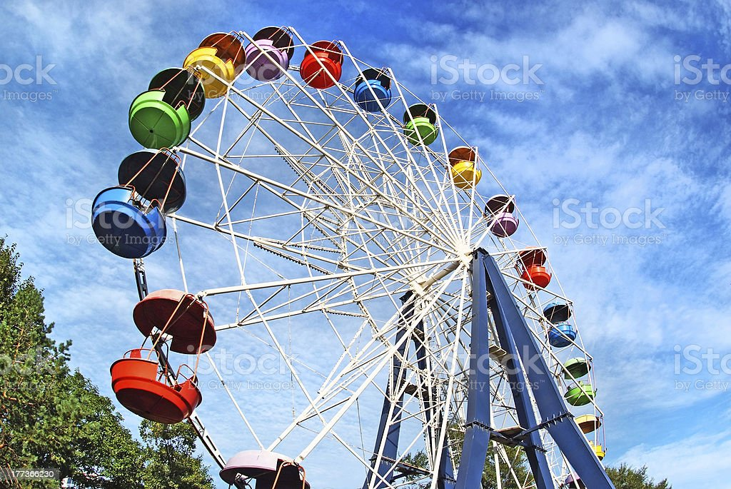 Brightly colored Ferris wheel against the blue sky stock photo
