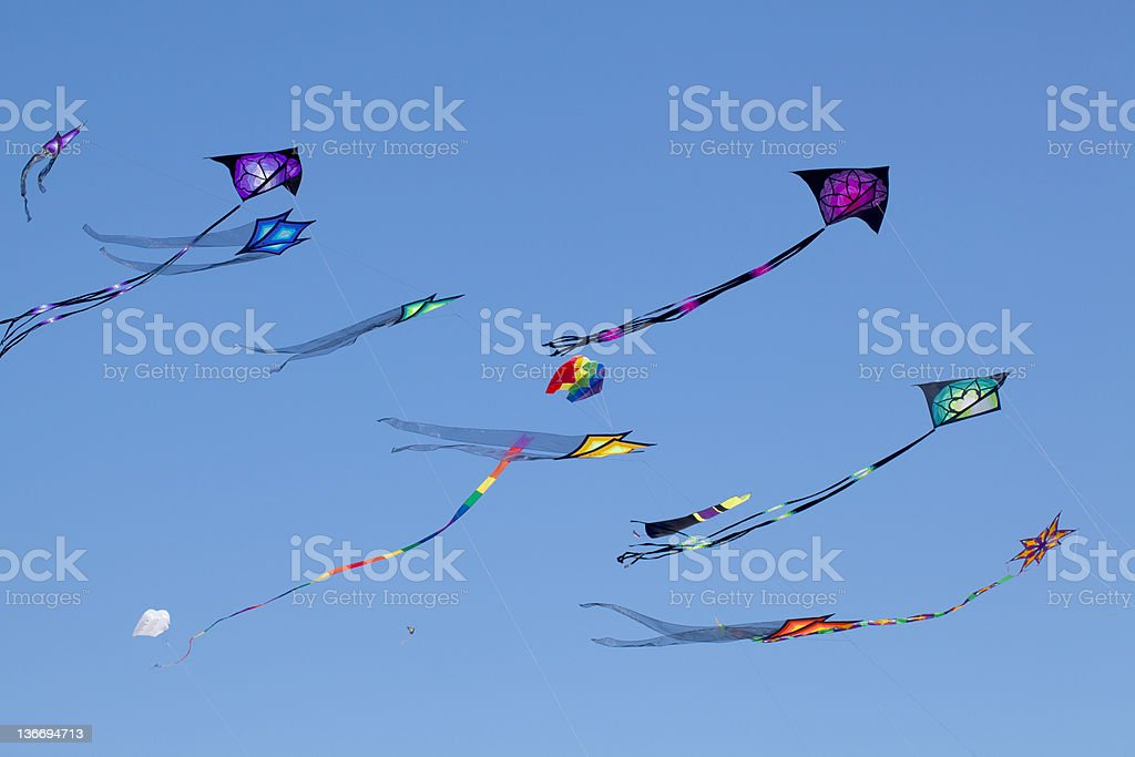 Brightly colored kites sailing against clear blue sky stock photo
