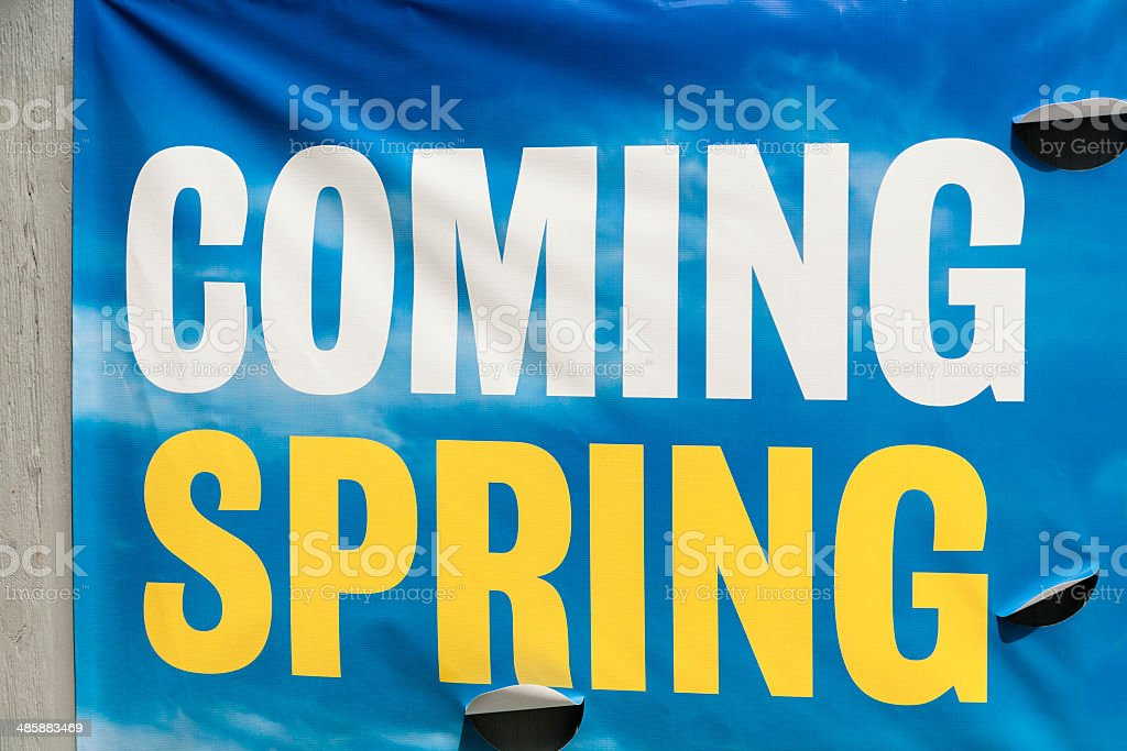 Brightly colored sign reads 'Coming Spring.'  Announcing new attraction. stock photo