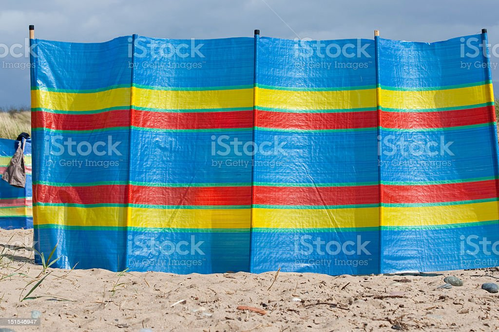 Brightly colored windbreak on the beach royalty-free stock photo