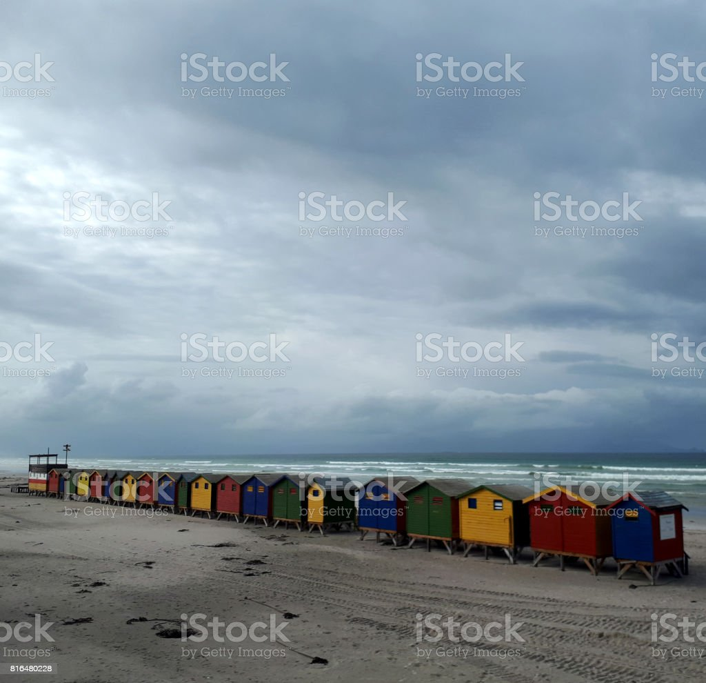 Brightly coloured beach huts under a winter sky stock photo