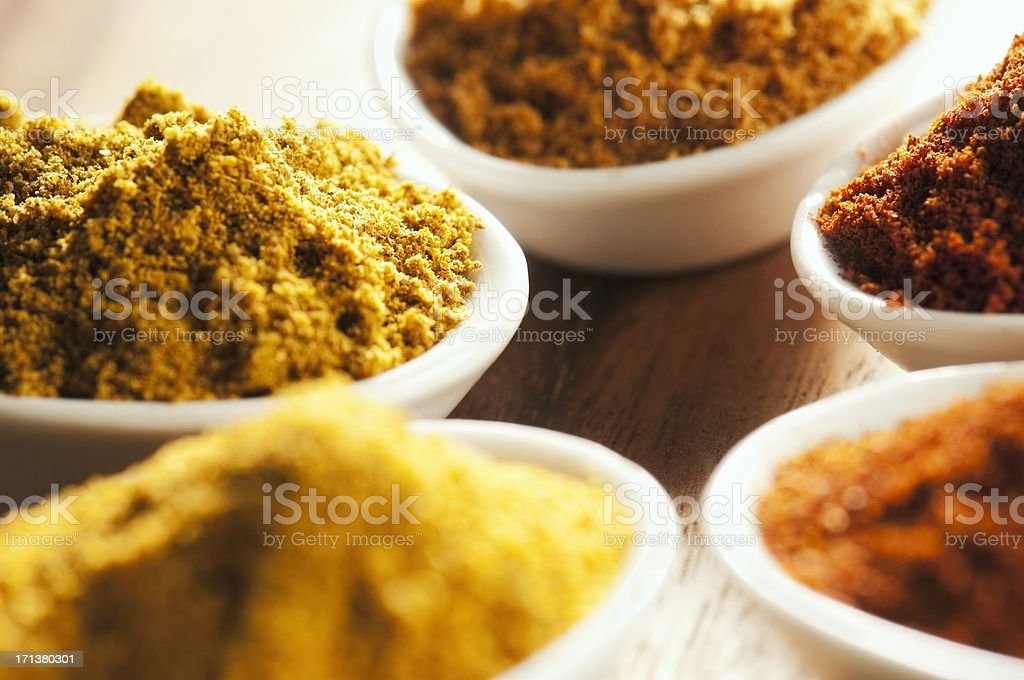 Brightly coloured ground cooking spices in white dishes royalty-free stock photo