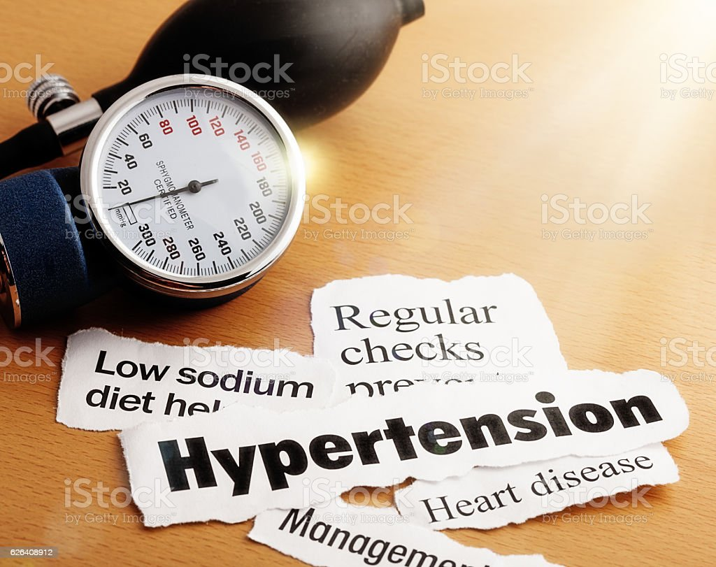 Brightly lit headlines on hypertension, with blood pressure meter stock photo
