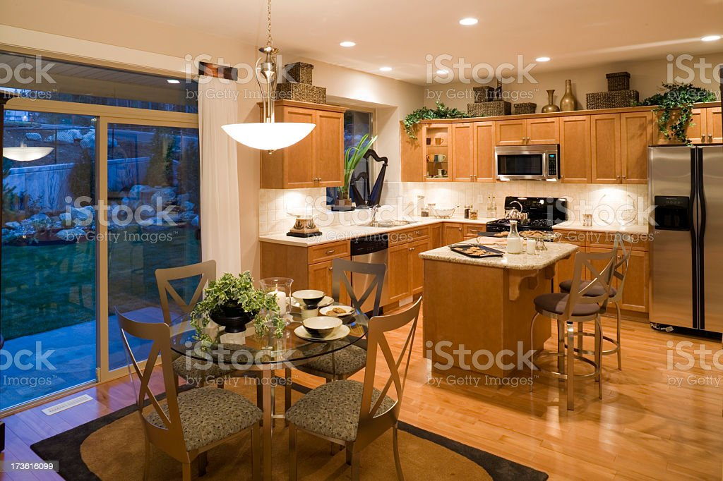 Brightly lit kitchen and dining room with birch cabinets royalty-free stock photo