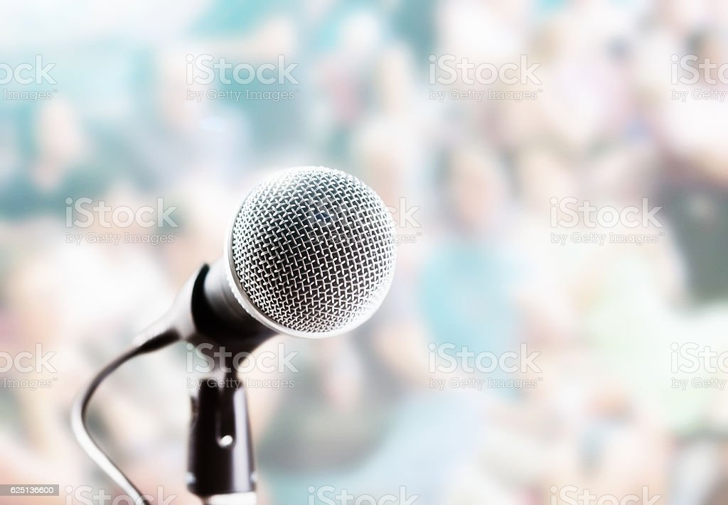 Brightly lit microphone in front of defocused audience stock photo