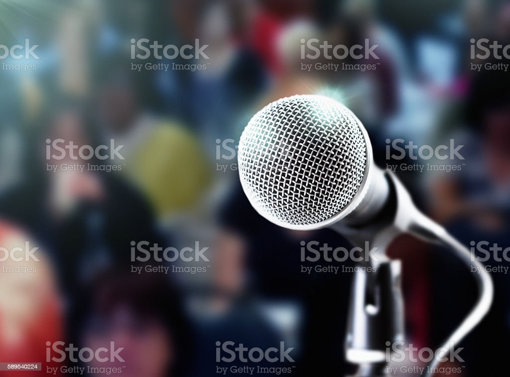 Brightly lit microphone with dark, defocused audience in the background stock photo