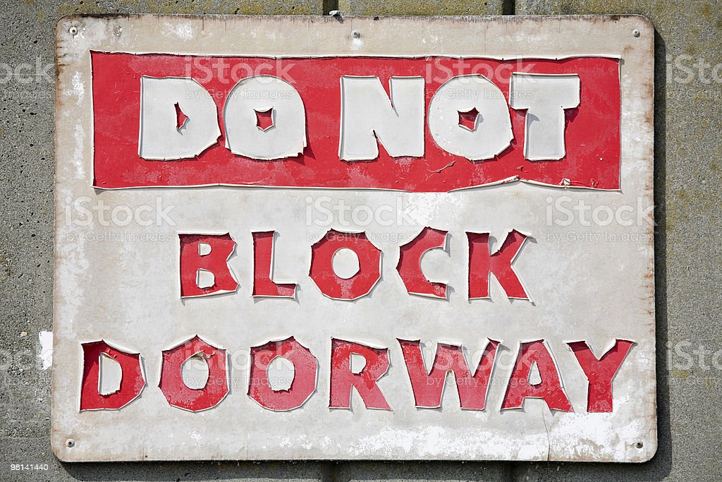 Brightly lit, old and faded Do Not Block Doorway sign stock photo
