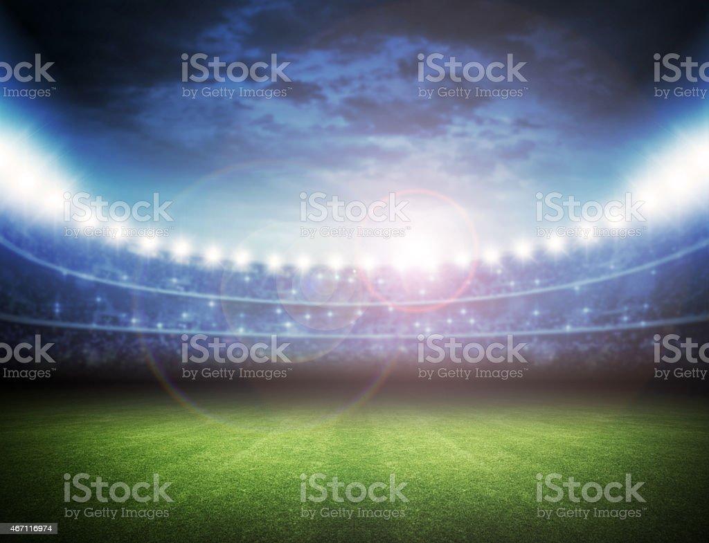 Brightly lit stadium with green grass stock photo