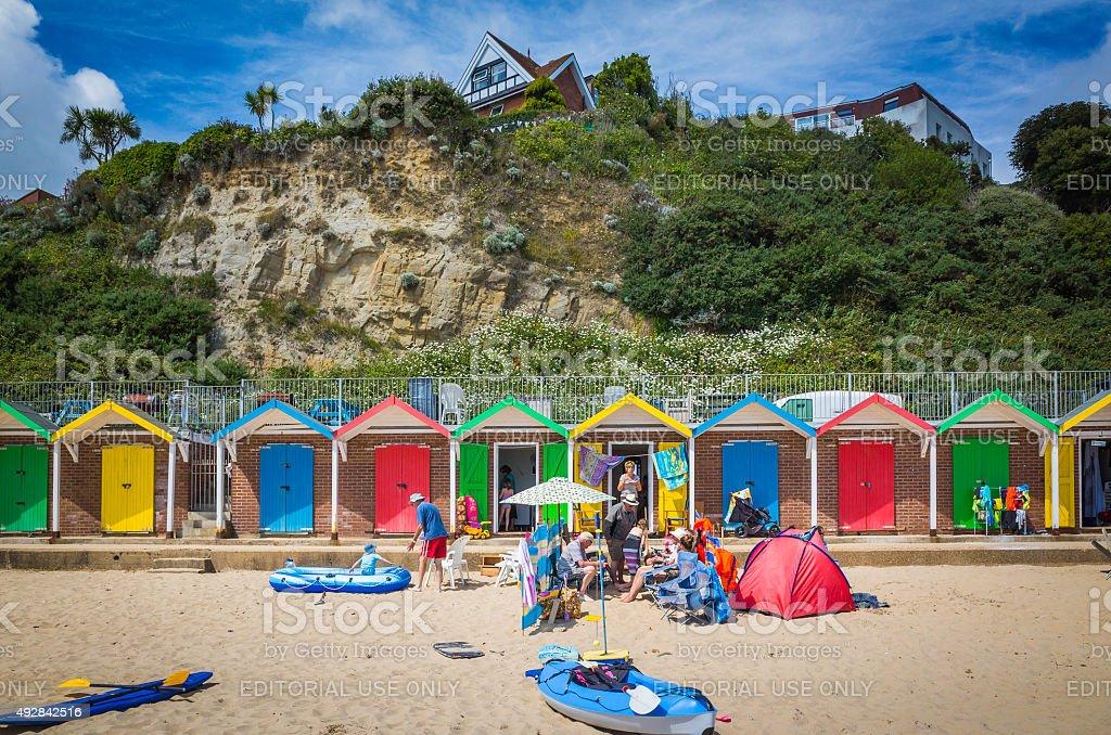 Brightly painted beach huts and families enjoying seaside sunshine England stock photo