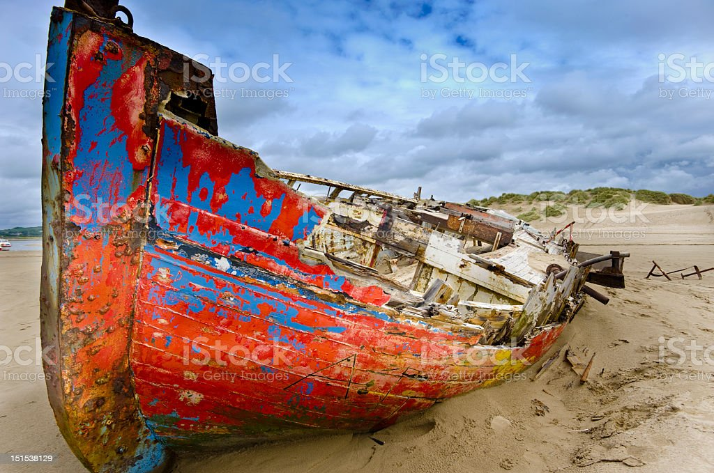 Brightly-colored boat wreck on a sandy beach stock photo