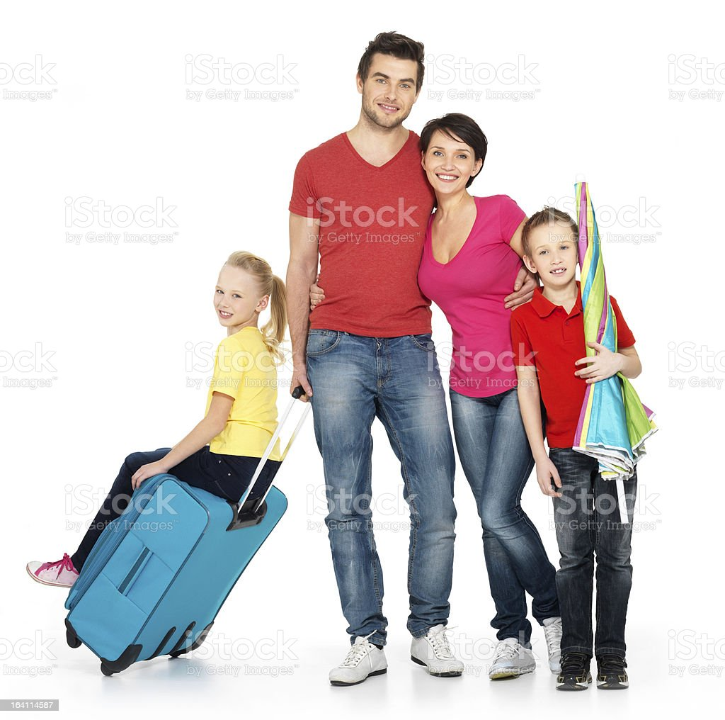 Brightly-dressed family with suitcase and sun umbrella stock photo
