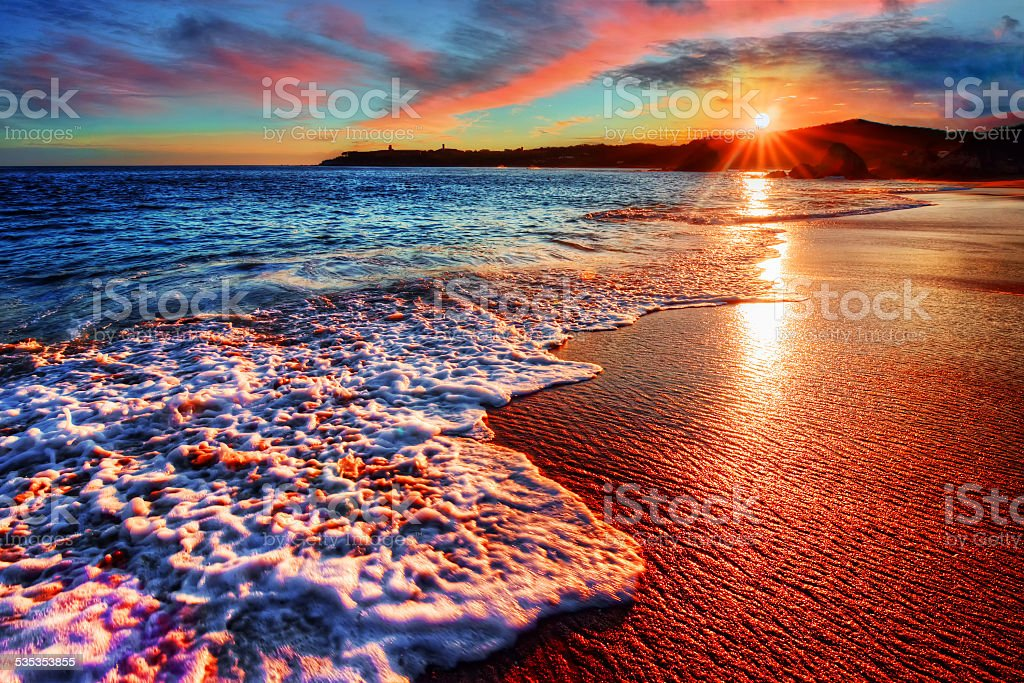 Brilliant vacation beach sunrise with colorful sand and distant cliffs stock photo