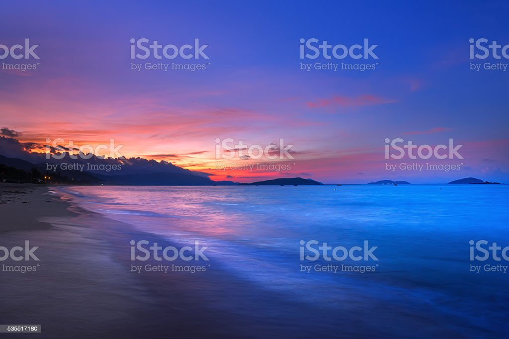 Brilliant vacation beach sunrise with colorful sand stock photo