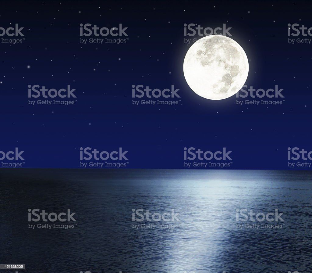Brilliantly glowing full moon reflecting light off the sea stock photo