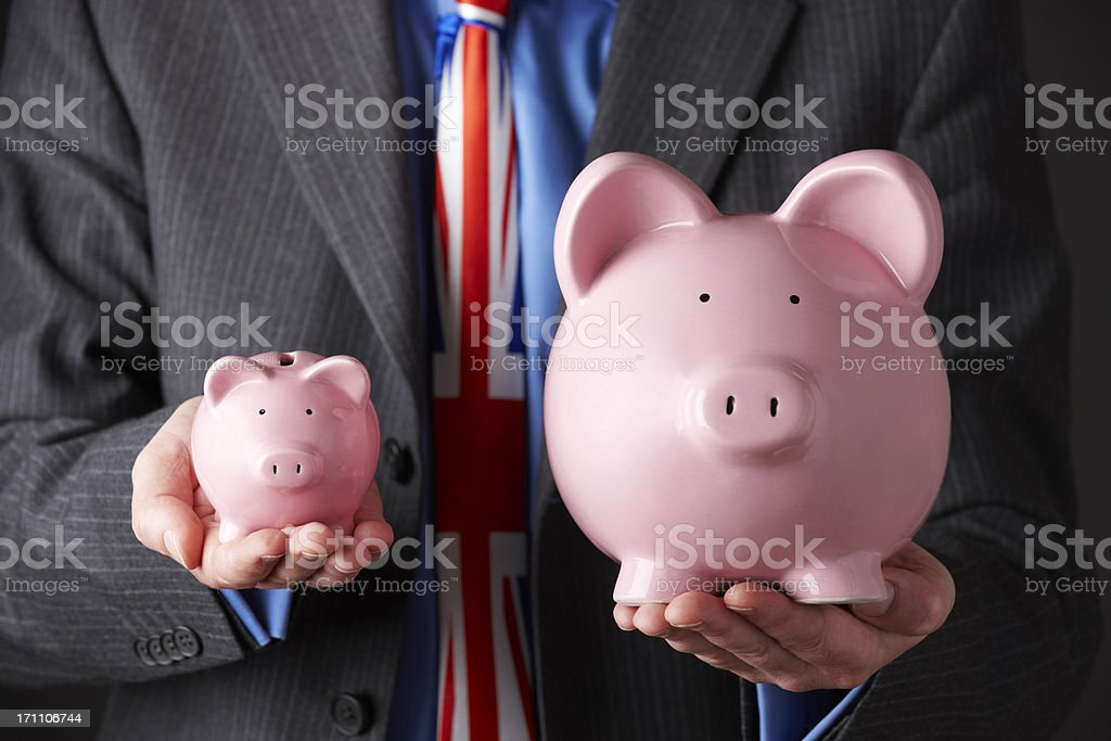 British Businessman Holding Large And Small Piggy Banks royalty-free stock photo