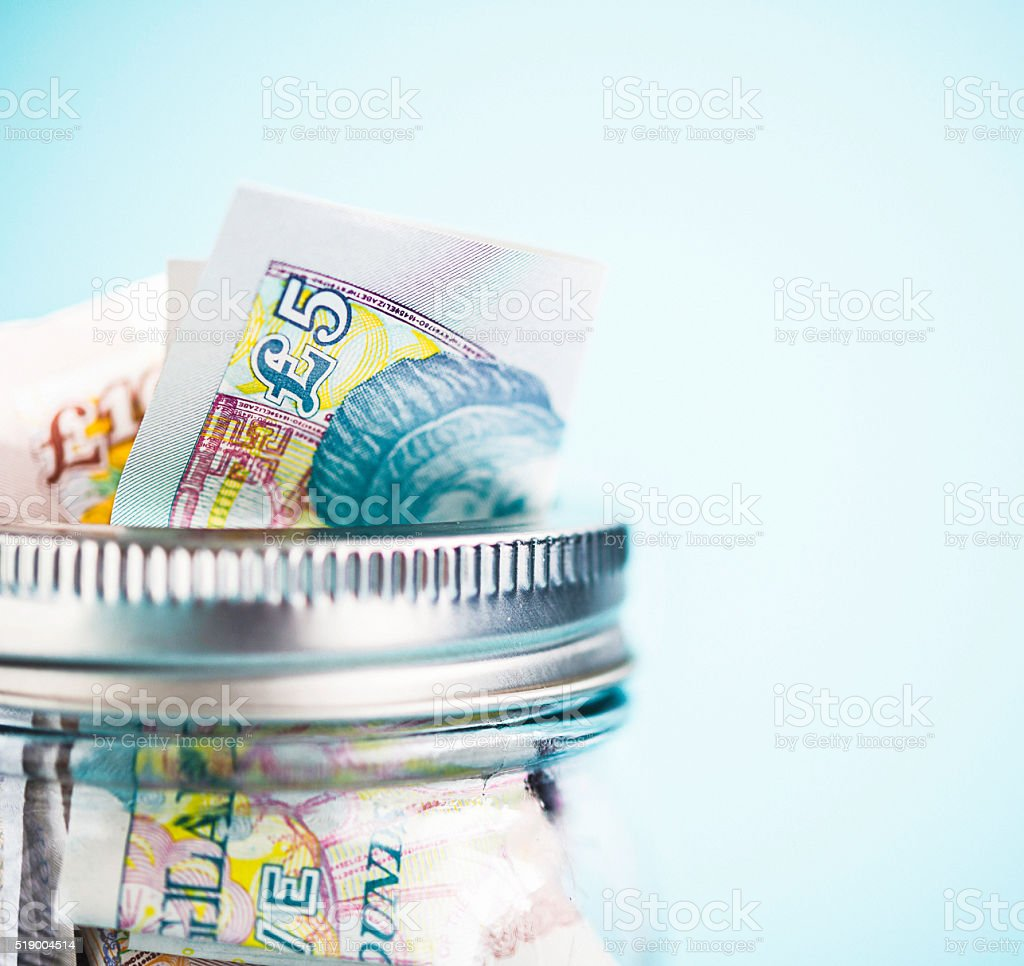 British currency in donation or savings jar stock photo