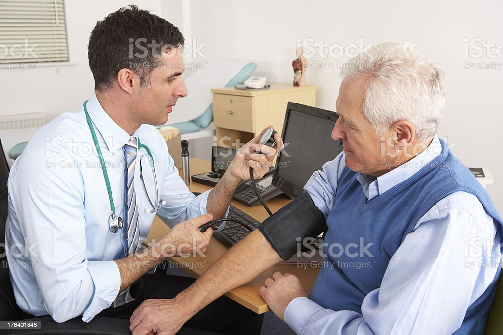 British doctor taking senior man's blood pressure stock photo