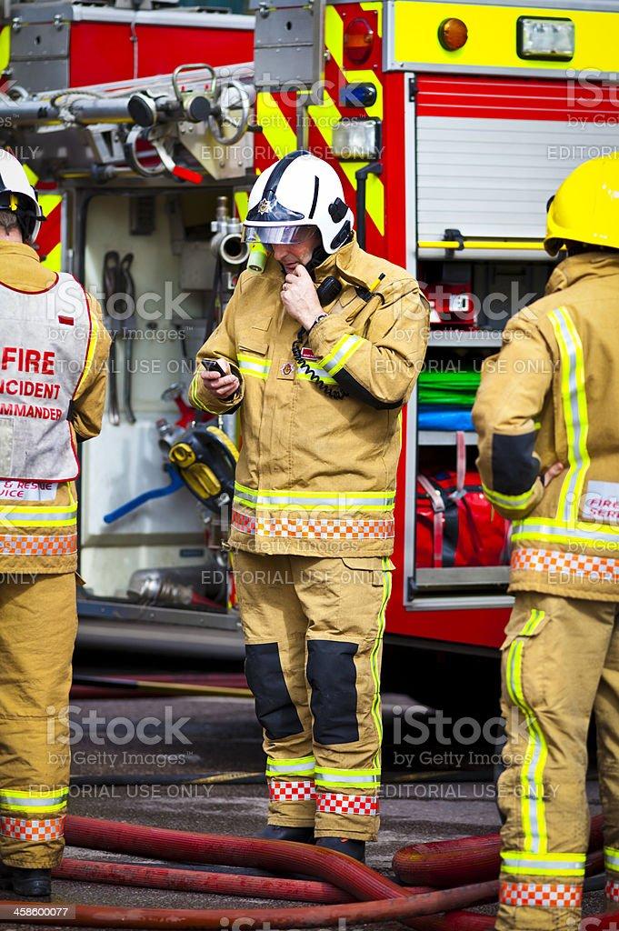 British firemen communicating at blaze scene stock photo