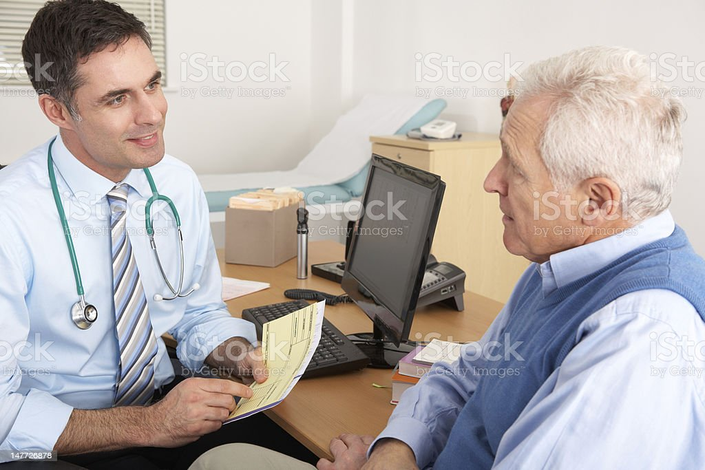 British GP talking to senior man in surgery stock photo