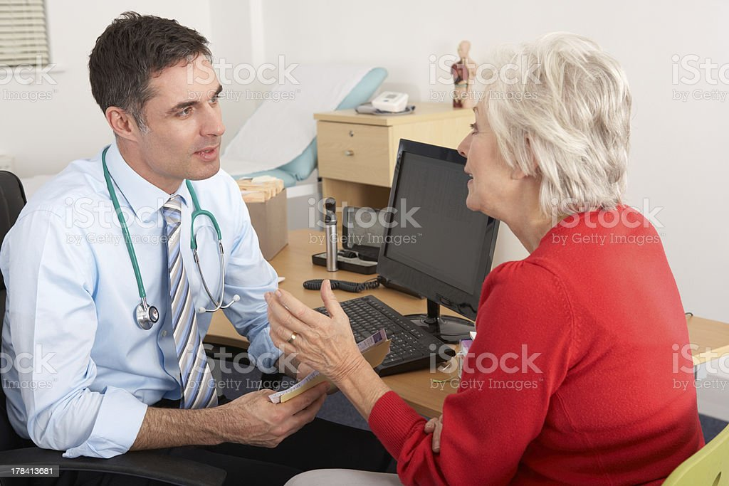 British GP talking to senior woman in surgery stock photo