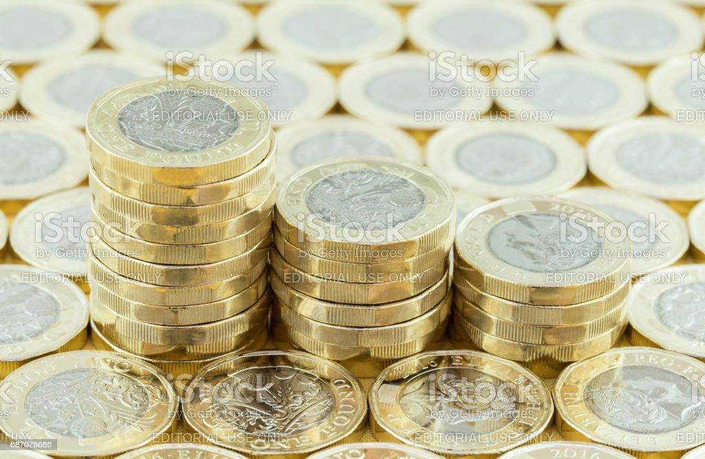 British money, new pound coins in three stacks. stock photo