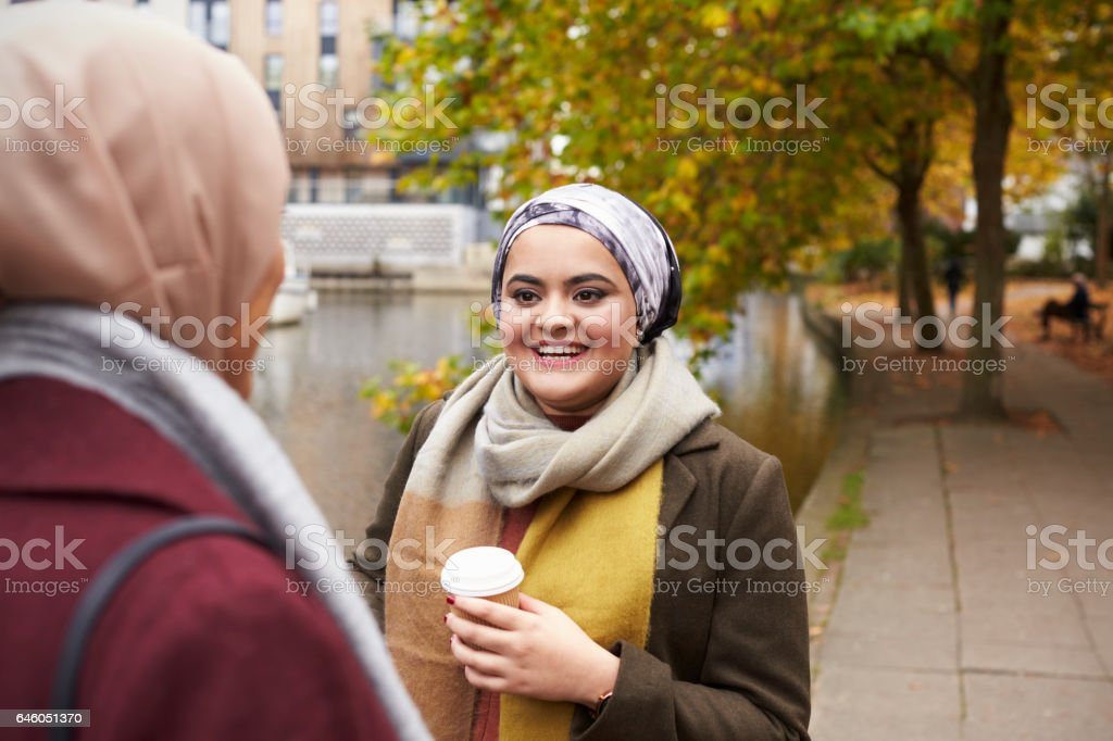 British Muslim Female Friends Talking By River In City stock photo