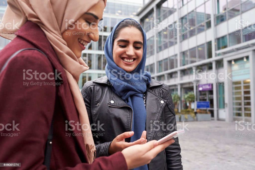 British Muslim Women Texting On Mobile Phone Outside Office stock photo